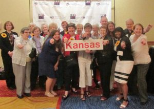 "Group of 20 adult men and women pose with sign that reads ""Kansas."" They are pointing at the camera."