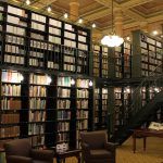 Stacks of books in historic library space.